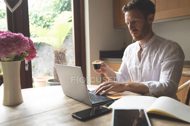 Man having coffee while using laptop at home — Stock Photo
