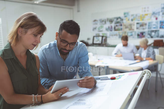Executives discussing over digital tablet on drafting table in office — Stock Photo