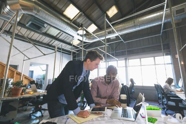 Compañeros de trabajo discutiendo sobre laptop en la oficina - foto de stock
