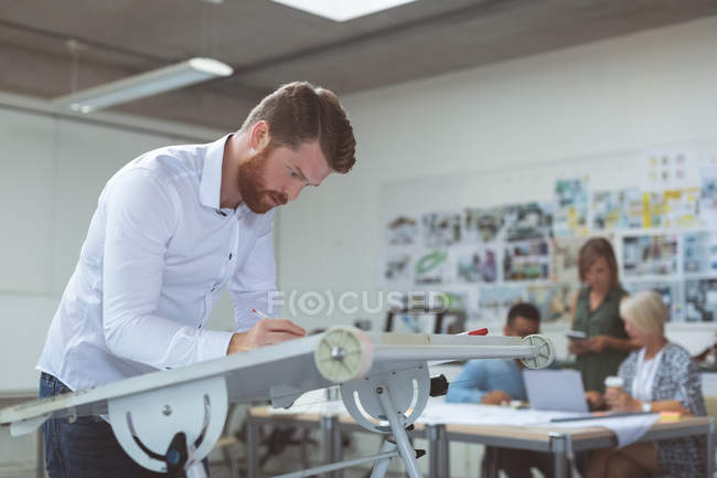 Executive working on drafting table in office — Stock Photo