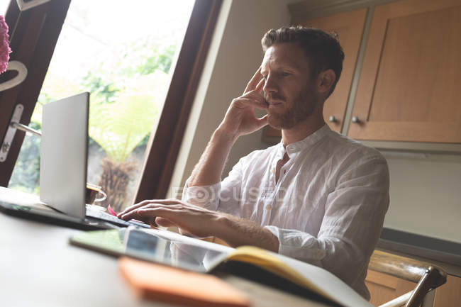 Thoughtful man using laptop at home — Stock Photo