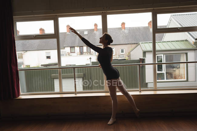 Ballerina practice arabesque ballet position in dance studio — Stock Photo