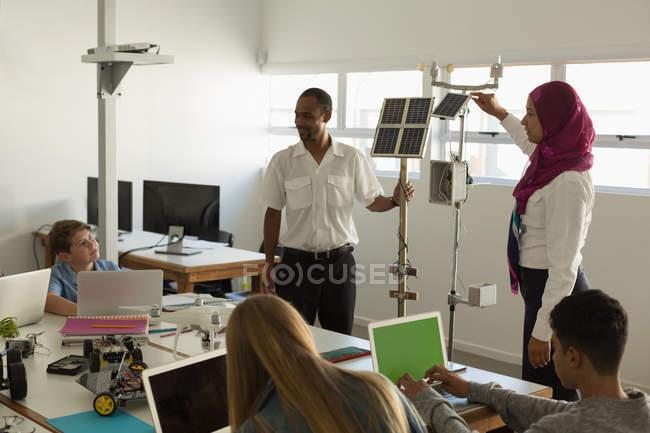 Formation des pilotes masculine et féminine sur panneau solaire aux étudiants en Institut de formation — Photo de stock
