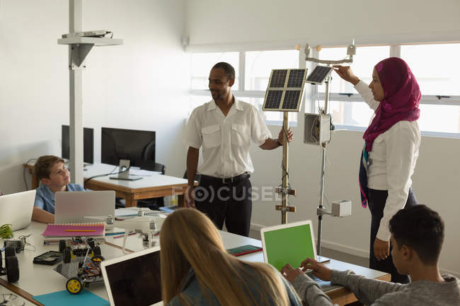 Male and female pilot training about solar panel to students in training institute — Stock Photo