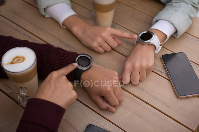 Close-up of couple using smartwatch at outdoor cafe — Stock Photo