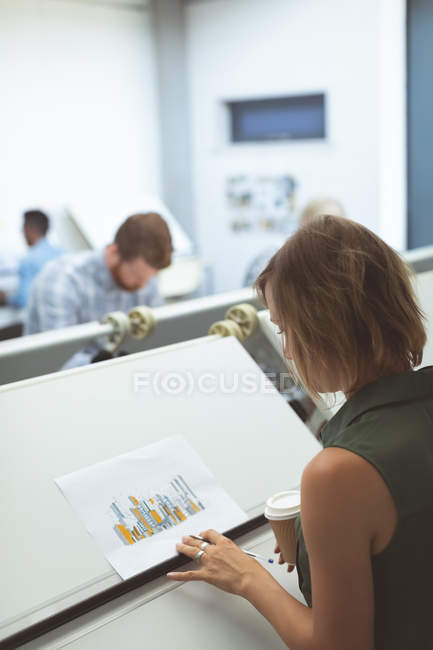 Female executive looking at blueprint on drafting table in office — Stock Photo