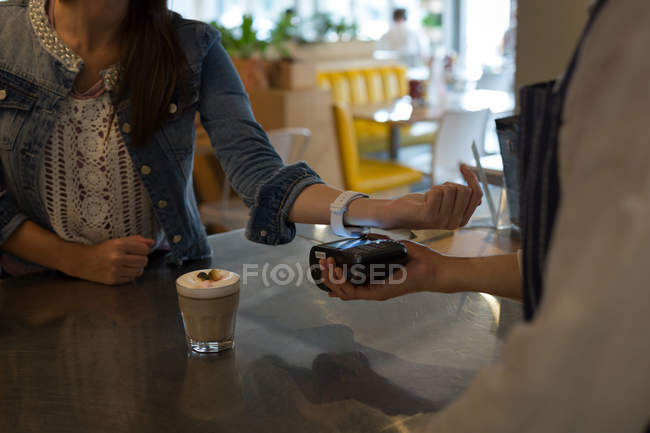 Mid section of woman paying with NFC technology on smartwatch in cafe — Stock Photo