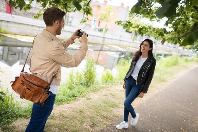 Mann klickt auf Bild einer Frau von Digitalkamera in der Nähe des Sees — Stockfoto
