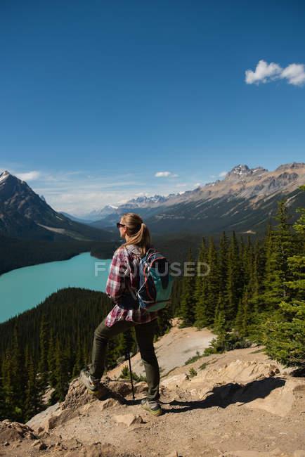Alpinista feminina em pé com a mochila no campo em um dia ensolarado — Fotografia de Stock