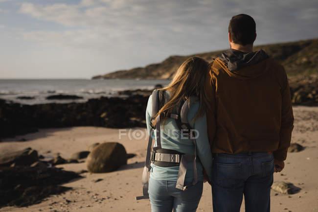Vue arrière du couple marchant sur la plage — Photo de stock