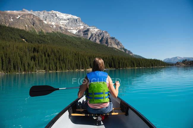 Vista posteriore della donna in barca a cavallo nel fiume — Foto stock