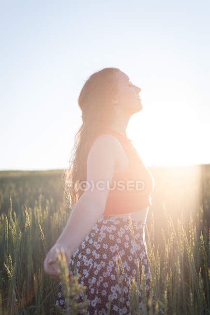 Young woman standing with arms outstretched in the field — Stock Photo