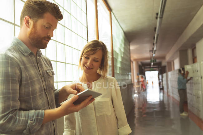 Executives discussing over digital tablet in corridor at office — Stock Photo