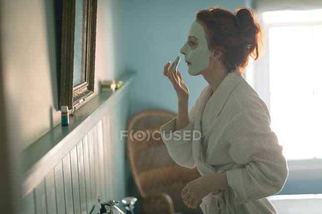Seitenansicht einer Frau, die zu Hause Gesichtsmaske aufträgt — Stockfoto