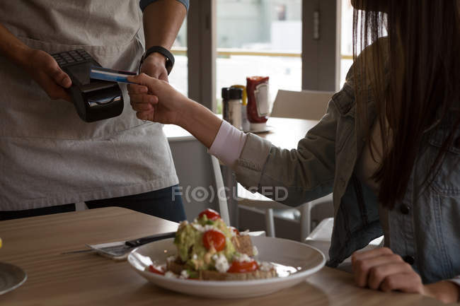 Woman paying with NFC technology on credit card in cafe — Stock Photo