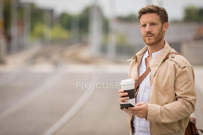 Uomo intelligente che utilizza il telefono cellulare in piattaforma alla stazione ferroviaria — Foto stock