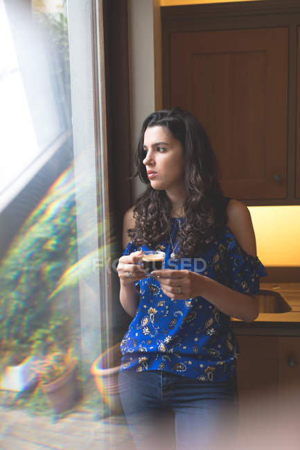 Bella donna che ha il caffè nero mentre in piedi vicino alla finestra a casa — Foto stock