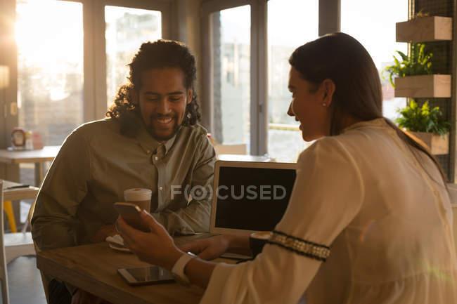 Молодая пара обсуждать на мобильном телефоне в кафе — стоковое фото