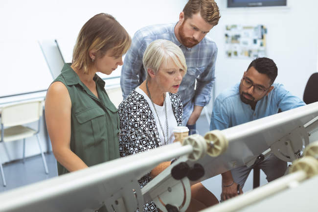 Executives discussing on drafting table in office — Stock Photo