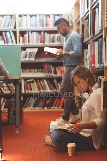 Attentive executives reading book in office library — Stock Photo