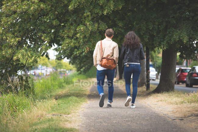 Vue arrière du couple marchant dans la rue dans la ville — Photo de stock