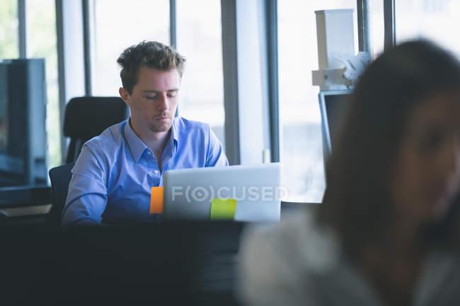 Esecutivo maschile che lavora su laptop alla scrivania in ufficio — Foto stock