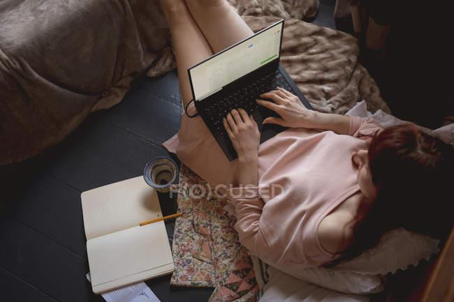 Высокоугольный вид женщины, использующей ноутбук дома — стоковое фото