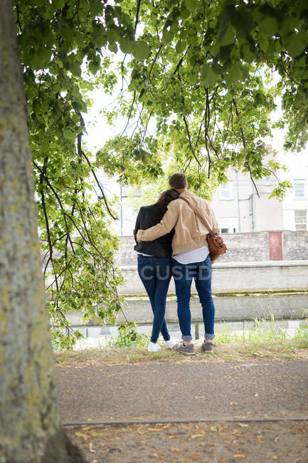 Rear view of couple standing near lakeside — Stock Photo
