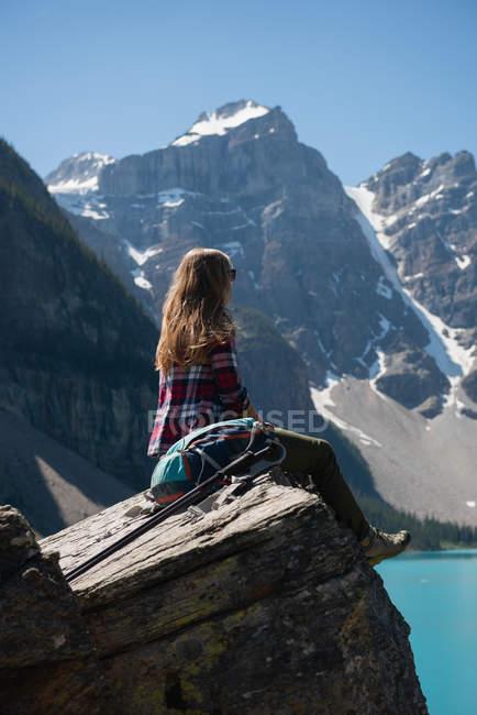 Молода жінка, сидячи на скелі поблизу Ріверсайд — стокове фото