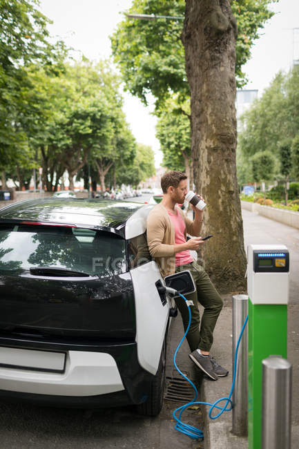 Man having coffee while using mobile phone at charging station — Stock Photo