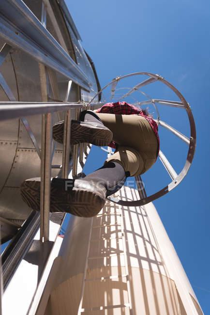 Blick in den niedrigen Winkel: Arbeiterin klettert auf Biogasanlage — Stockfoto