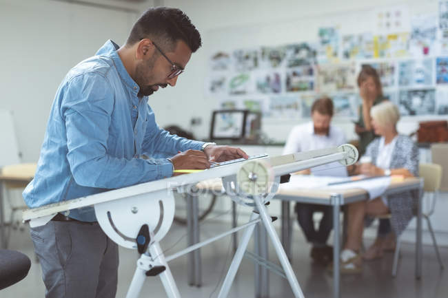 Male executive working over drafting table in office — Stock Photo