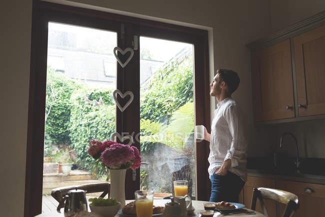 Продуманий людина за кавою, поки стоїть біля вікна будинку — стокове фото
