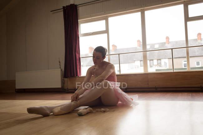 Linda bailarina amarrando laço de sapato no estúdio de dança — Fotografia de Stock