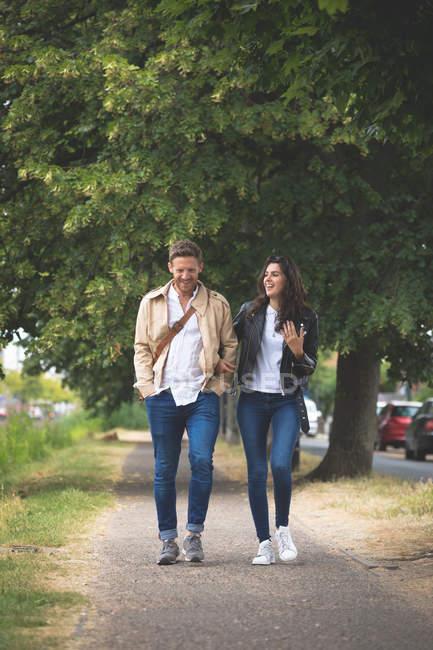 Счастливая пара взаимодействует во время прогулки по улице — стоковое фото
