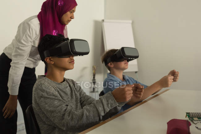 Female pilot giving training on virtual reality headset to students in training institute — Stock Photo
