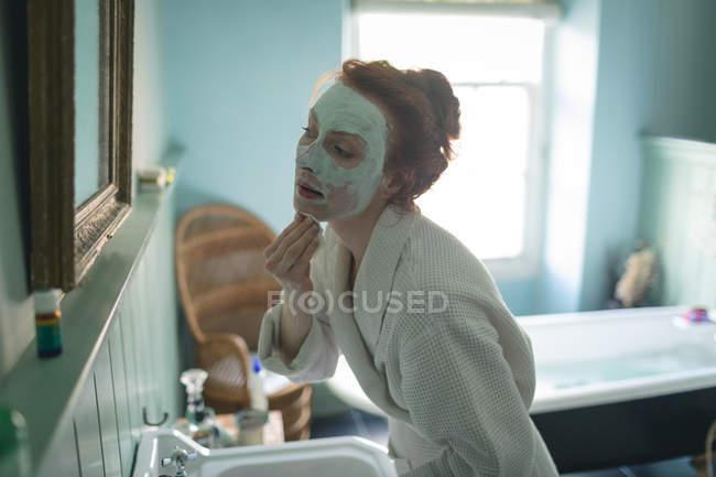 Frau entfernt Gesichtsmaske vor Spiegel im heimischen Badezimmer — Stockfoto