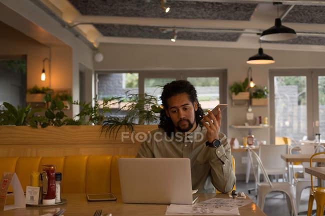 Человек, говорят на мобильном телефоне при использовании ноутбука в кафе — стоковое фото