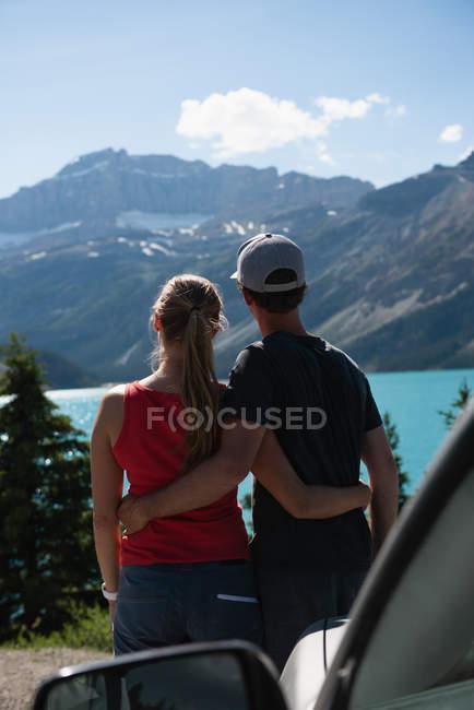 Rückansicht eines Pärchens, das mit Arm in der Landschaft steht — Stockfoto
