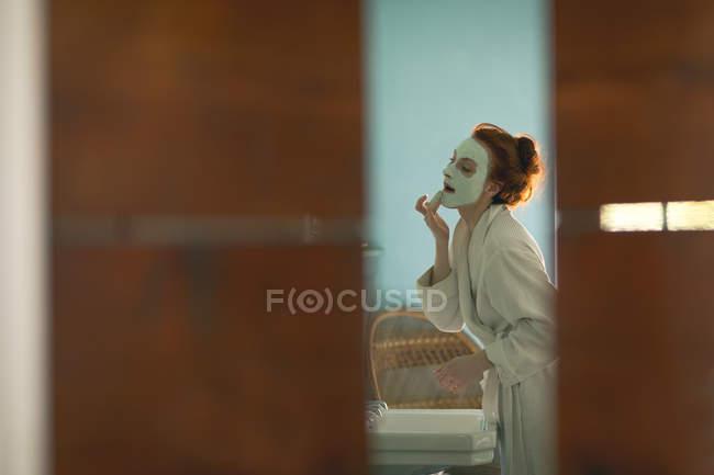 Frau trägt Gesichtsmaske zu Hause auf — Stockfoto