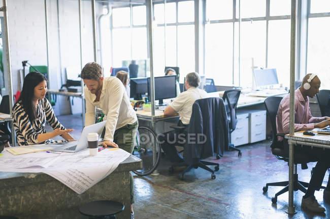 Des collègues d'affaires discutent sur ordinateur portable au bureau — Photo de stock