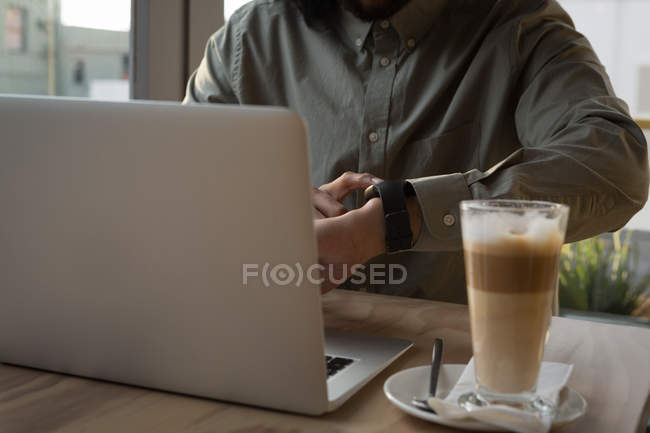 Mid section of man using smartwatch in cafe — Stock Photo