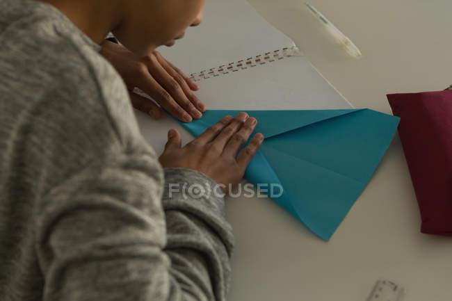 Gros plan de kid faire avion en papier avec du papier craft en Institut de formation — Photo de stock
