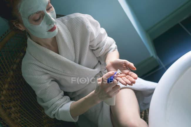 Frau cremt sich zu Hause im Badezimmer ein — Stockfoto