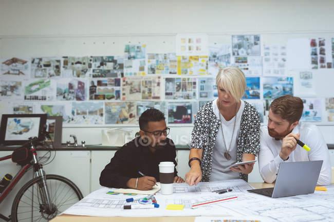 Ejecutivos discutiendo sobre el plano en el escritorio en la oficina - foto de stock