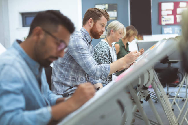 Executives working on drafting table in office — Stock Photo