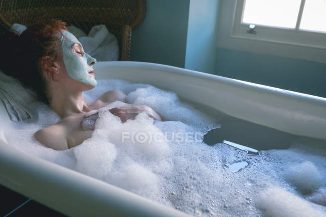 Woman relaxing in bathtub at bathroom — Stock Photo