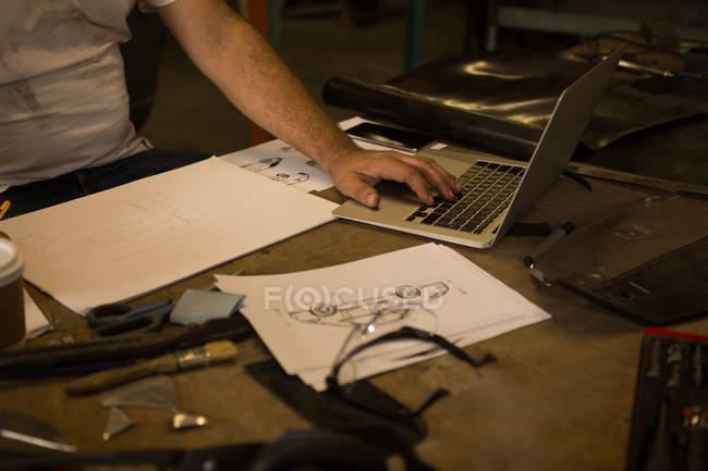 Розділ середині чоловічого механік, використовуючи ноутбук у гаражі — стокове фото