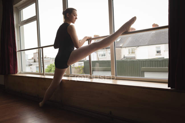 Ballerina stretching on barre while practicing ballet dance in dance studio — Stock Photo