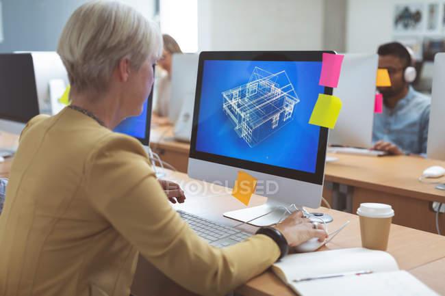 Donna d'affari che lavora su PC desktop alla scrivania in ufficio — Foto stock